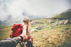 Couple travelers Man and Woman follow holding hands. At foggy mountains landscape on background Love and Travel happy emotions Lifestyle concept. Young family Royalty Free Stock Photography