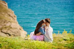 Young couple in love, Attractive man and woman enjoying romantic evening on the beach watching the sunset. Couple Travelers Man and Woman sitting relax in a hike Stock Photo