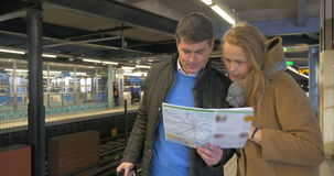Couple of travelers with map in subway. Man and woman tourists in underground. They looking at city or metro guide and trying to undesrtand where to go. Train stock footage