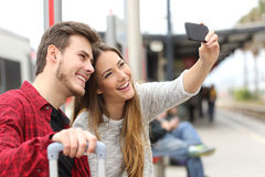 Couple of travelers photographing a selfie with a smartphone. In a train station Royalty Free Stock Photos