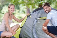 Free Couple Travelers Putting Cover On Tent They Assemble Royalty Free Stock Images - 186145909
