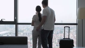 Couple travelers with suitcase is entering in hotel room with panoramic city view. Young couple travelers with suitcase is entering in hotel room with panoramic stock video