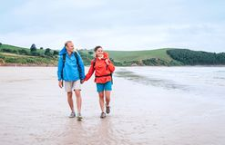 Couple travelers walk on the coast of Biskay Bay in North Spain, part of camino del Norte famous piligrims route royalty free stock photos