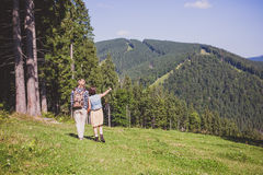 Couple of travelers walking at the summer meadow. And looking around mountain view Royalty Free Stock Photos