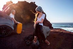 Couple traveling by car. Young and pretty couple dressed alike enjoying their travel near the car on the rocky coast on the sunset Royalty Free Stock Photos