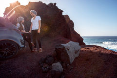 Couple traveling by car. Young and pretty couple dressed alike enjoying their travel near the car on the rocky coast on the sunset Stock Photography