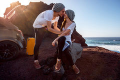 Couple traveling by car. Young and pretty couple dressed alike kissing near the car on the rocky coast on the sunset Royalty Free Stock Image