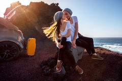 Couple traveling by car. Young and pretty couple dressed alike kissing near the car on the rocky coast on the sunset Stock Photos