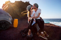 Couple traveling by car. Young and pretty couple dressed alike kissing near the car on the rocky coast on the sunset Stock Images