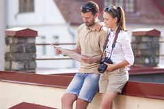 Couple Traveling Through the City.Posing Embraced Sitting on Fence Outdoors Stock Photo