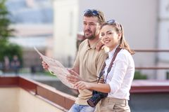 Couple Traveling Through the City.Posing Embraced Sitting on Fence Stock Image
