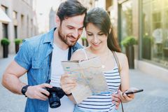 Couple traveling in europe using map and cellular. Young tourists couple in the street visiting city royalty free stock photography