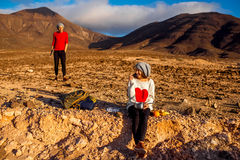 Couple traveling Fuerteventura island. Young couple travelers working with laptop and having small picnic on the desert mountain landscape on Fuerteventura Royalty Free Stock Photos