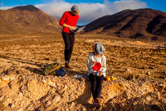 Couple traveling Fuerteventura island. Young couple travelers working with laptop and having small picnic on the desert mountain landscape on Fuerteventura Stock Photography