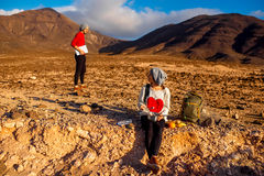Couple traveling Fuerteventura island. Young couple travelers working with laptop and having small picnic on the desert mountain landscape on Fuerteventura Royalty Free Stock Photo
