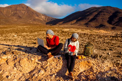 Couple traveling Fuerteventura island. Young couple travelers working with laptop and having small picnic on the desert mountain landscape on Fuerteventura Stock Photo