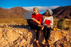 Couple traveling Fuerteventura island. Young couple travelers working with laptop and having small picnic on the desert mountain landscape on Fuerteventura Stock Photos