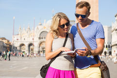 Couple traveling and reading tourist guide Stock Images