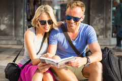 Couple traveling and reading tourist guide book Royalty Free Stock Photography
