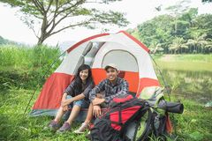 Couple traveling and spending time while camping. Two couple traveling and spending time near tent. Happy people in camping Royalty Free Stock Photo