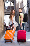 Couple  traveling with suitcases. Young couple traveling with suitcases on a European city Stock Images