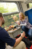 Couple traveling by train eating sandwiches hungry Royalty Free Stock Photo