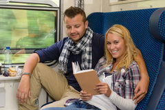 Couple traveling by train woman reading smiling Stock Images