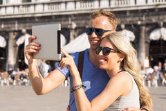 Couple traveling and using tablet computer Stock Photography