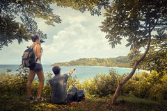 Couple travellers with backpacks watching through binoculars enj. Couple tourists with backpacks enjoying view coast island Lombok on top of a mountain Royalty Free Stock Photo