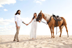 Couple of travellers  holding hands, walking through desert on horse Stock Photos