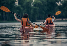 Couple travelling by kayak. Happy young couple in sea vests is sailing kayaks Stock Images