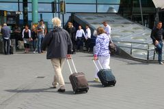 Couple Travels With Hand Luggage From Amsterdam Schiphol Airport, Netherlands Stock Photo