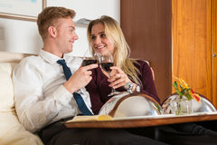 Couple with tray of wine and food in hotel room Royalty Free Stock Image