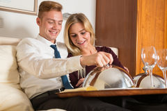 Couple with tray of wine and food in hotel room Stock Photos