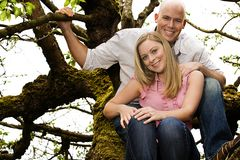 Couple in a tree. A cute young couple climbing a tree Royalty Free Stock Photos