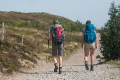 Couple of trekkers walking at the top with backpack Stock Photography