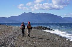 Couple Trekking On Beach Stock Images
