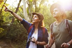 Couple trekking together into forest Stock Image