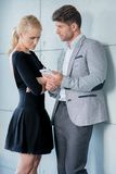 Couple in Trendy Attire Talking Something at Phone Stock Image