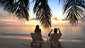 Couple on a tropical beach are admiring the sunset. Young Couple on a tropical beach are admiring the sunset. Maldives stock footage