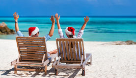 Couple at tropical beach. Back view of a happy couple in Santa hats relaxing on a tropical beach during Christmas vacation, panorama perfect for banners Royalty Free Stock Photos