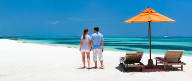 Couple at tropical beach. Back view of a couple on a tropical beach vacation panorama perfect for banners Stock Images