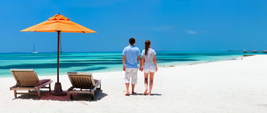 Couple at tropical beach. Back view of a couple on a tropical beach vacation panorama perfect for banners Royalty Free Stock Image