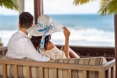 Couple on a tropical beach in chaise lounge. Looking at sea, back view Stock Photos
