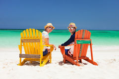 Couple at tropical beach. Happy couple sitting on colorful chairs at tropical beach enjoying Caribbean vacation Stock Photo