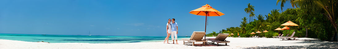 Couple at tropical beach. Romantic couple on a tropical beach during honeymoon vacation, super wide panorama perfect for banners Stock Photos