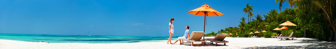 Couple at tropical beach. Romantic couple on a tropical beach during honeymoon vacation, super wide panorama perfect for banners Royalty Free Stock Images