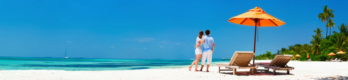 Couple at tropical beach. Romantic couple on a tropical beach during honeymoon vacation, wide panorama perfect for banners Stock Photos