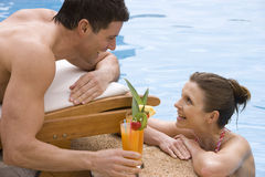 Couple with tropical drink at edge of swimming pool Stock Image
