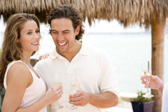 Couple at a tropical hotel bar, having a drink royalty free stock image